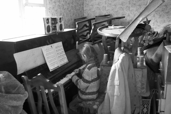 A small girl plays piano in a village bombed by the Russians