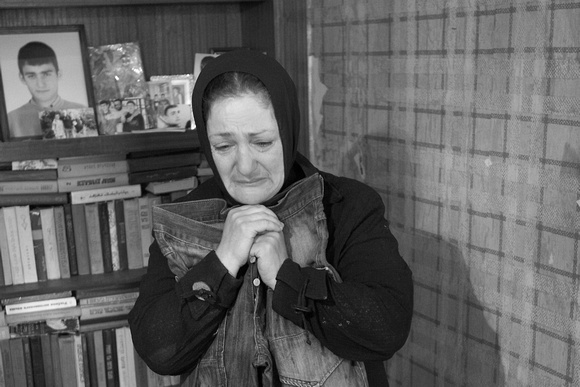 She is clutching the blood-soaked jeans of her son, killed by a Russian rocket attack on their house